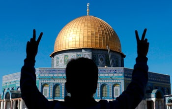 """A Palestinian youth flashes the V-sign for """"victory"""" during Friday prayers in front of the Dome of the Rock mosque at the Al-Aqsa mosque compound in Jerusalem's Old City on December 8, 2017"""