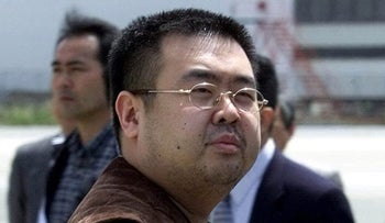 In this May 4, 2001, file photo, a man believed to be Kim Jong Nam, the eldest son of then North Korean leader Kim Jong Il, looks at a battery of photographers as he exits a police van to board a plane to Beijing at Narita international airport in Narita, northeast of Tokyo.