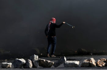 A Palestinian demonstrator uses a sling to hurl stones at Israeli troops during clashes near the Jewish settlement of Beit El, near the West Bank city of Ramallah. December 11, 2017
