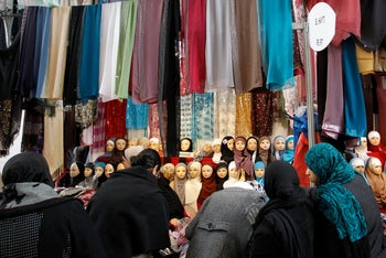 Women look at veils at an exhibition hall for the Muslim World Fair in Le Bourget, outside Paris.