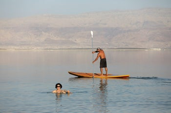 A woman floating near a man as he paddles on a board in the Dead Sea in Ein Bokeq, February 20, 2017.