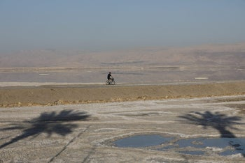 A man cycling near the shore of the Dead Sea in Ein Bokeq, February 20, 2017.