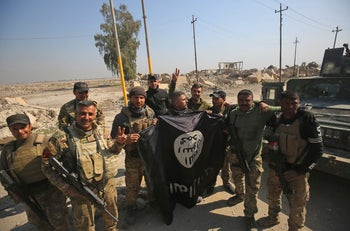 Iraqi forces celebrating while holding an Islamic State flag as they enter Mosul airport, February 23, 2017.