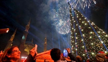 People take photos of fireworks during an event to turn on the lights of a Christmas tree in downtown Beirut on December 10, 2017