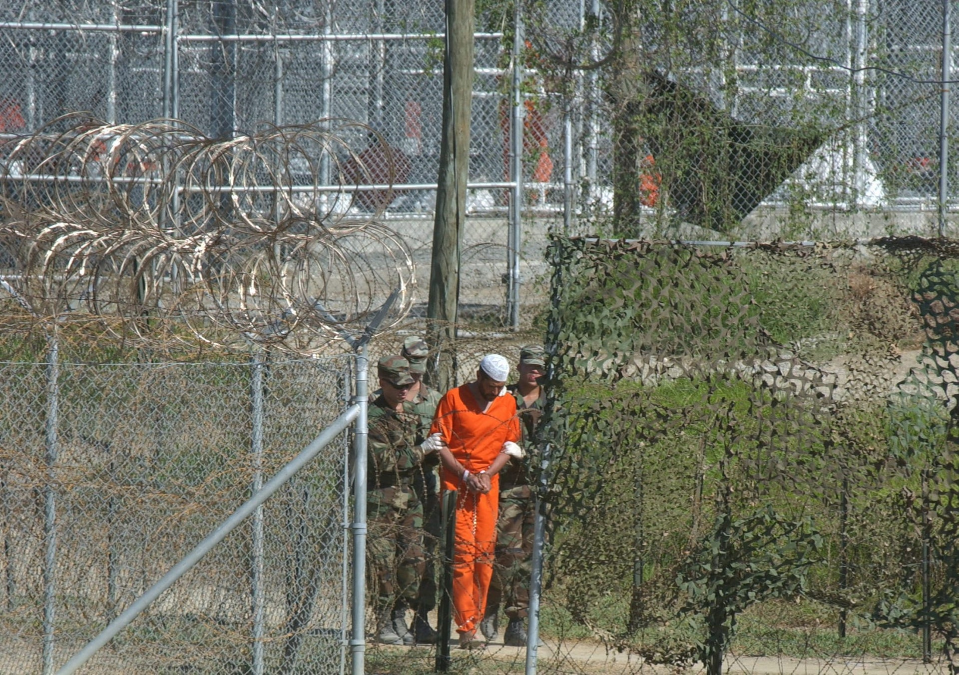 A detainee is escorted to interrogation by U.S. military guards at Camp X-Ray at Guantanamo Ba, Cuba, March 1, 2002.