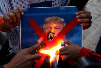 Palestinian youths set a portrait of US President Donald Trump on fire after his  recognition of Jerusalem as Israel's capital, during a demonstration outside Damascus Gate in Jerusalem's Old City on December 11, 2017