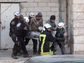 Syrian civil defence volunteers, known as the White Helmets, carry a comrade who was injured in an air strike in the rebel-held town of Binnish, on the outskirts of Idlib, on February 25, 2017.