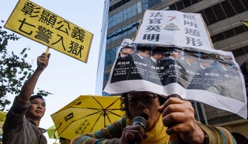 A photo from February 17, 2017 shows an activist outside the Hong Kong District Court holding an image of seven police officers found guilty of assaulting an activist in 2014.