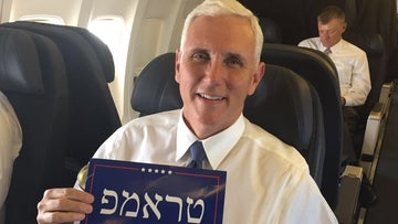 "A photograph of Republican vice presidential candidate Mike Pence holding a poster that says ""Make America Great Again"" in Hebrew."