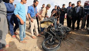 Palestinians inspect the damaged remains of a motorcycle, that was reportedly hit by an Israeli strike according to the Palestinian health ministry spokesman, in Beit Lahia in northern Gaza strip on December 12, 2017