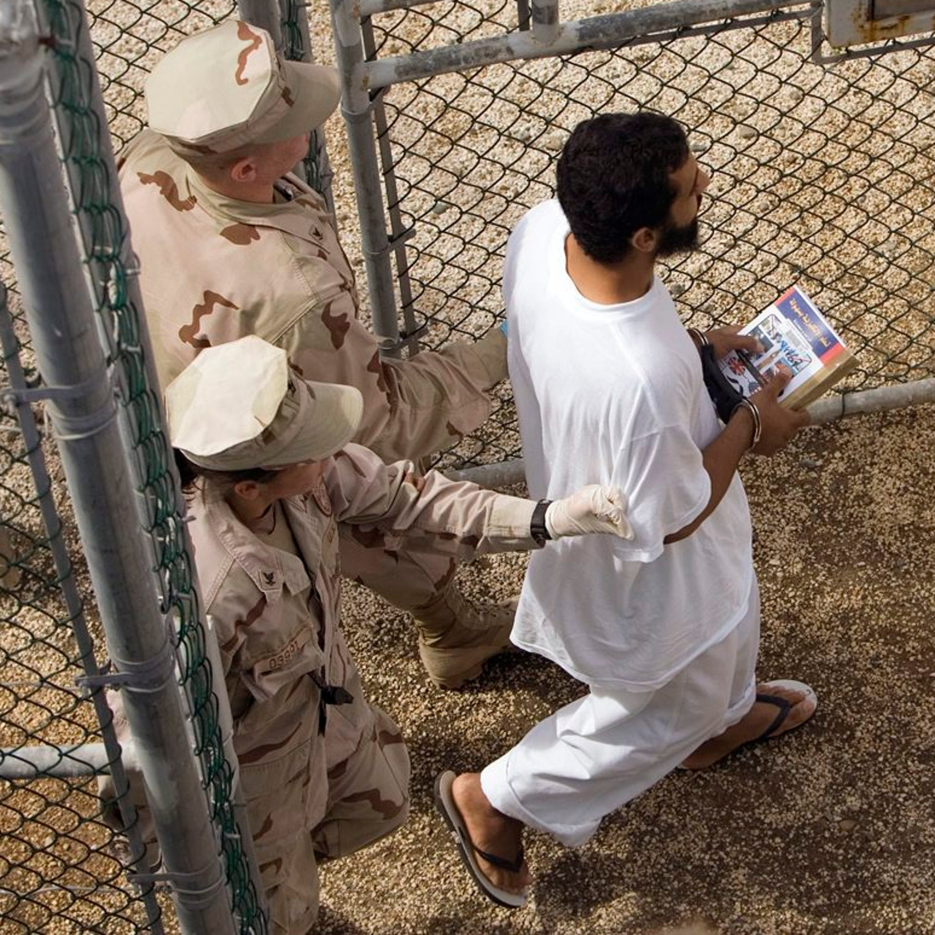 In this 2008 file image, guards escort a Guantanamo detainee carrying a book at the Camp 4 detention facility in Guantanamo Bay, Cuba.