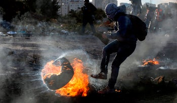 A Palestinian protester kicks a flaming tire during clashes with Israeli forces in the West Bank city of Ramallah, December 11, 2017.