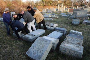 Men help lift a fallen tombstone at the Jewish Mount Carmel Cemetery, February 26, 2017, in Philadelphia, PA.