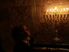 Lighting the seventh candle, Hanukkah December 12, 2015. Picture shows a young child, his features somewhat blurred, looking at a menorah on which seven candles have been lit plus the shamash. The menorah has the classic modern shape with four branches on each side and the shamash stem in the middle.