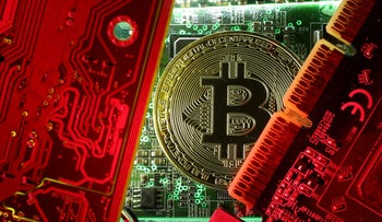 FILE PHOTO: A coin representing the bitcoin cryptocurrency is seen on computer circuit boards in this illustration picture, October 26, 2017.