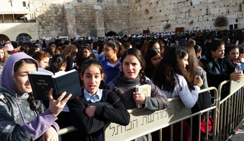 Religious high school girls on other side of a barricade watching Women of the Wall worshippers at the Western Wall on February 27, 2017.