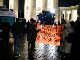 Protesters hold a placard during the demonstration outside the U.S. embassy against President Donald Trump's decision to recognize Jerusalem as Israel's capital in Berlin, Germany, December 8, 2017.