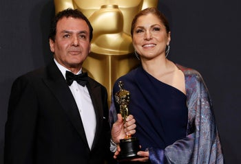 """Firouz Naderi and Anousheh Ansari posing with the Oscar they accepted on behalf of director Asghar Farhadi, who won the Best Foreign Language Film for """"The Salesman."""""""