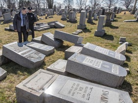 Northeast Philadelphia Police Detective Timothy McIntyre and a Philadelphia police officer look over tombstones that were vandalized at Mount Carmel Cemetery on Sunday, Feb. 26, 2017, in Philadelphia.