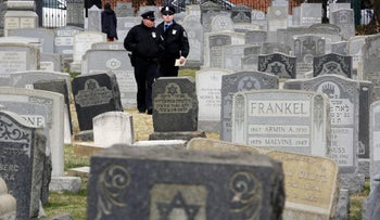 Philadelphia Police walk through Mount Carmel Cemetery after more than 100 headstones were vandalized, February 27, 2017.