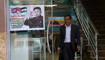 A Palestinian customer walks out of a shawarma restaurant with a poster of North Korean leader Jim Jong at the entrance of it in Jebaliya refugee camp, Gaza Strip, Thursday, Dec. 14, 2017.