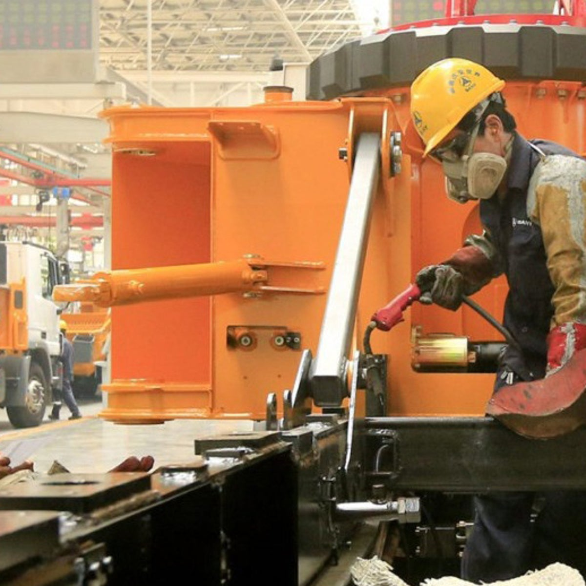 Employees work on the manufacture of construction machinery in Sany Heavy Industry Co.'s assembly shop in Changsha, Hunan Province, China, on Thursday, July 12, 2012. Sany Heavy Industry, Chinas biggest maker of excavators, lowered annual unit-sales forecast as slowing economic growth and government's curbs on property market sap demand.