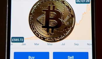 A gold plated souvenir Bitcoin coin is arranged for a photograph on a smart phone displaying current value of a single bitcoin, and options to buy or sell, on an app for the digital asset broker, Coinbase, in London on November 20, 2017.