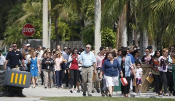 People being evacuated because of a bomb threat return to the David Posnack Jewish Community Center and David Posnack Jewish Day School, Monday, Feb. 27, 2017, in Davie, Florida.