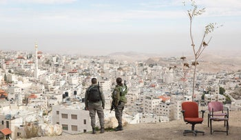 In this Sunday, Dec. 10, 2017 photo, Israeli border police officers overlooking the Arab neighborhood of Issawiyah in Jerusalem