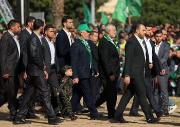 Hamas leader Ismail Haniya (C-R) and Hamas' leader in the Gaza Strip Yahya Sinwar (C-L) arrive for a rally marking the 30th anniversary of the founding of the Islamist movement, in Gaza City, on December 14, 2017.  /