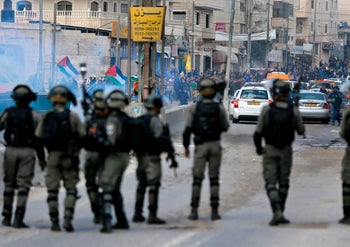 Israeli security forces stand guard as Palestinian protesters gather in the West Bank city of Ramallah, December 15, 2017.