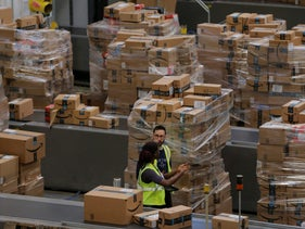 Workers walk past boxes at an Amazon center in Robbinsville, New Jersey, November 27, 2017.