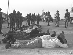 Israeli troops guarding captured Egyptians and Palestinians lying on a roadside at Rafah during the Six-Day War, June 1967.