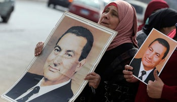 Supporters of former Egyptian President Hosni Mubarak hold up his pictures as they wait for him to be transferred to a court, in front of Maadi military hospital in Cairo, Egypt, March 2, 2017.