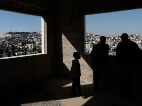 A Palestinian man and child standing inside a West Bank building cut off from Jerusalem by the West Bank separation barrier.