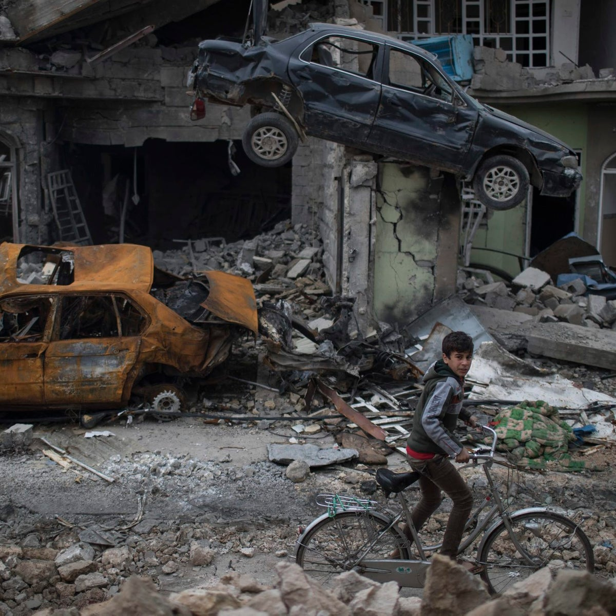 A boy rides his bike past destroyed cars and houses in a neighborhood recently liberated by Iraqi security forces on the western side of Mosul, Iraq, Sunday, March 19, 2017.