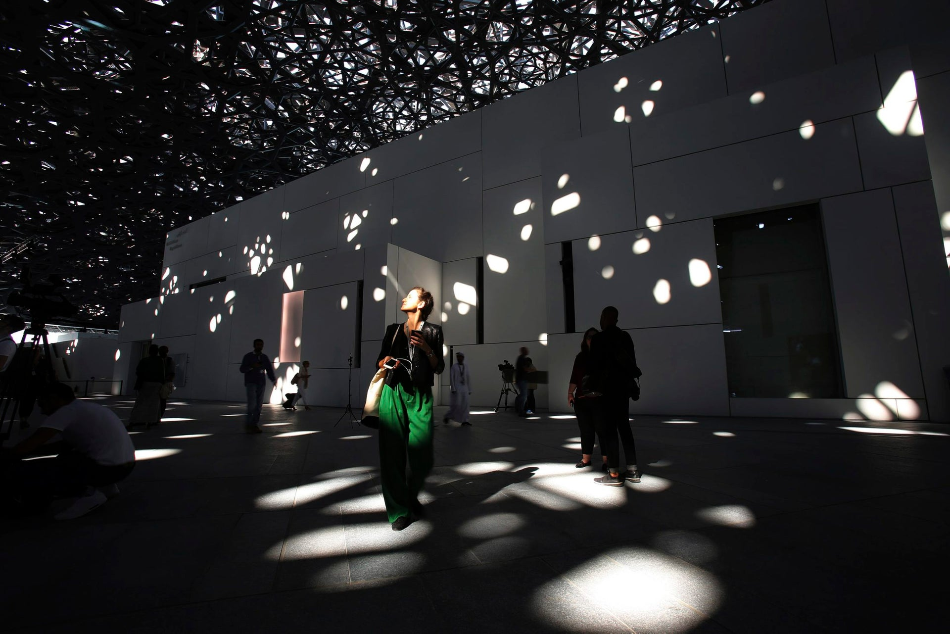 A journalist walks under the lights coming through of the dome at the Louvre Abu Dhabi, United Arab Emirates, Nov. 6, 2017. The Louvre Abu Dhabi is preparing its grand opening _ unveiling its treasures to the world after a decade-long wait and questions over laborers' rights. The museum, which opens on Saturday to the public, encompasses work from both the East and West.