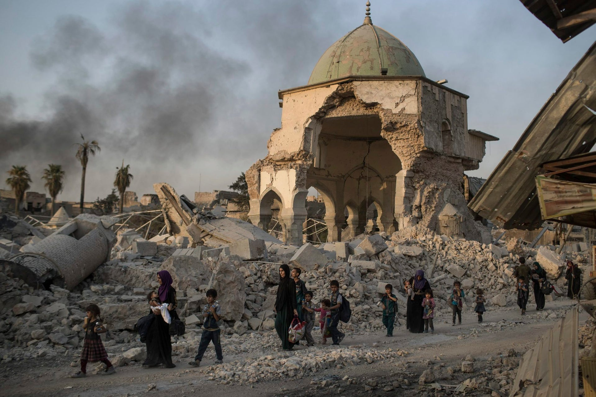 Iraqi civilians fleeing walk past the destroyed al-Nuri mosque as Iraqi forces continue their advance against Islamic State militants in the Old City of Mosul, Iraq, Tuesday, July 4, 2017.