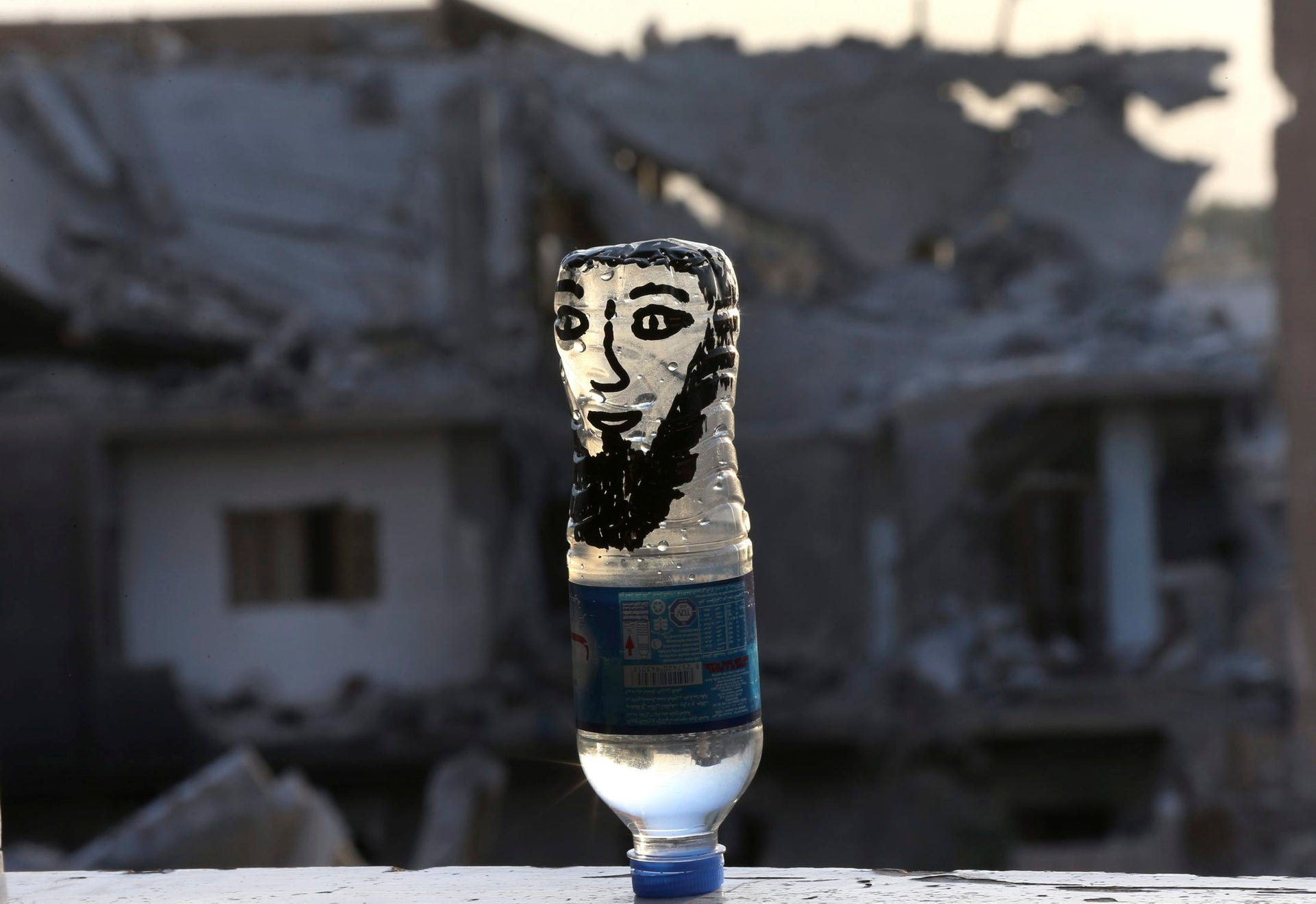 A water bottle painted with a face to represent an Islamic State fighter, left by U.S.-backed Syrian Democratic Forces fighters on a window sill, on the front line, in Raqqa city, northeast Syria, Thursday, July 27, 2017.