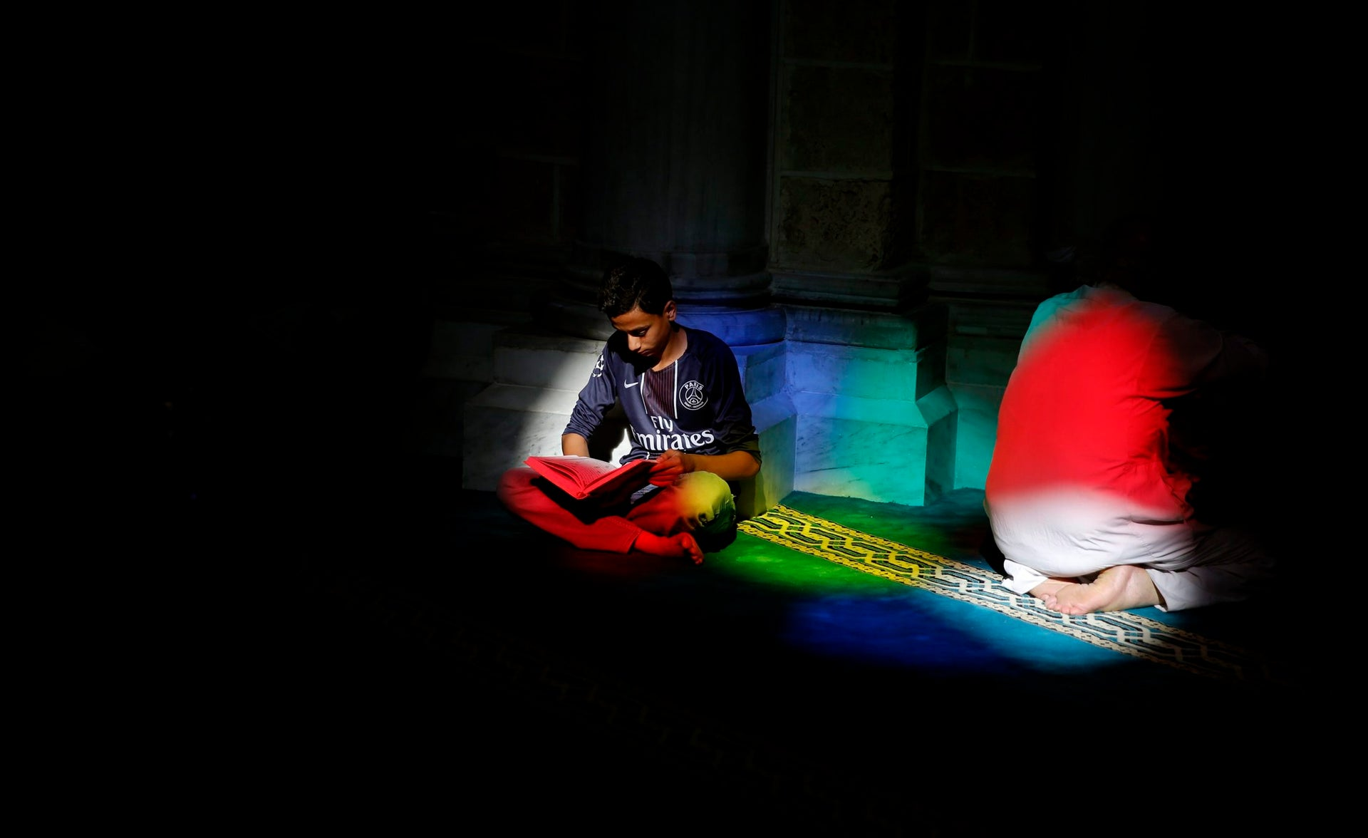 A Palestinian man reads verses of the Quran, Islam's holy book, during the month of Ramadan at Al Emari mosque in Gaza City, Monday, May 29, 2017.