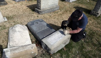 Trump supporter Bob, who declined to give his last name, volunteers his time and prepares the base of a damaged headstone Tuesday, Feb. 28, 2017, at a vandalized Jewish cemetery in Philadelphia.
