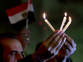 People hold candles and national flags during a candlelight vigil for victims of a Friday mosque attack in Cairo, Egypt on November 27, 2017.