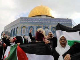 People hold Palestinian flags as they protest after Friday prayers at the Temple Mount in Jerusalem, December 15, 2017.