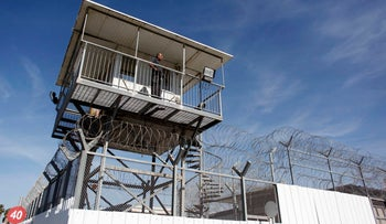 FILE PHOTO: An Israeli prison guard keeps watch from a tower at Ayalon prison in Ramle near Tel Aviv February 13, 2013