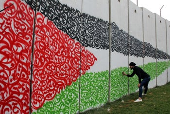 An artist draws the Palestinian flag on a wall on the southern Lebanese border with Israel near Fatima's Gate in response to the United States' Jerusalem decision. December 17, 2017