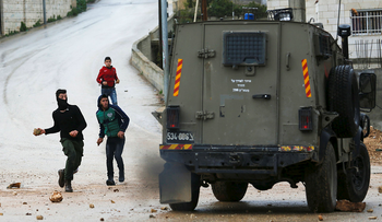 Palestinian protesters hurl stones at an Israeli military vehicle in the West Bank village of Nabi Saleh near Ramallah, Friday, March 3, 2017.