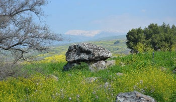 The giant dolmen, with a 50-ton capstone and a carved ceiling unique in the Middle East, found by Kibbutz Shamir, dates to more than 4,000 years ago. Mt. Hermon can be seen in the background, with snow on its cap.