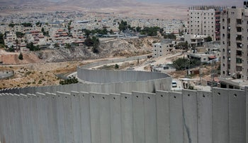A file photo of Israel's separation wall in East Jerusalem with cement wall in foreground, buildings in background.
