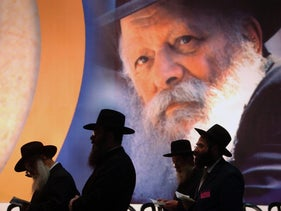 Chabadniks praying in Tel Aviv on the backdrop of a huge poster showing Lubavitcher Rebbe Menachem Mendel Schneerson, in 2004.