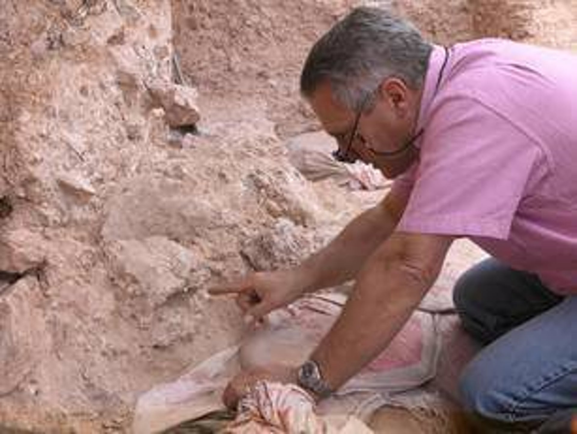 Jean-Jacques Hublin at Jebel Irhoud (Morocco), pointing to the crushed human skull whose orbits are visible just beyond his finger tip.